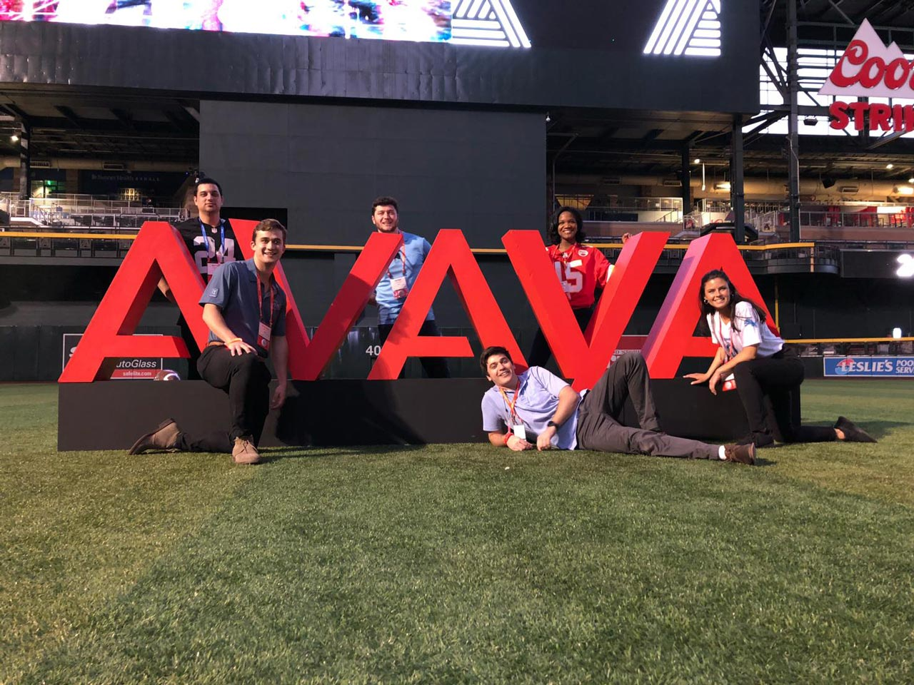 Avaya team members at a statue of large Avaya logo