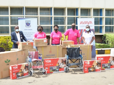 Avaya employees posing in front of donations for charity