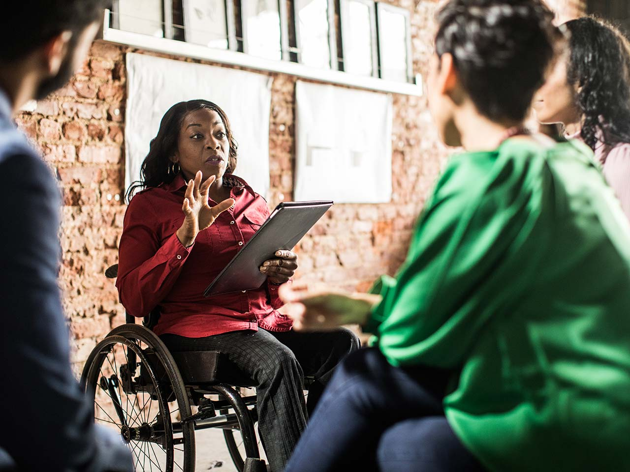 Woman in wheelchair talking to coworkers