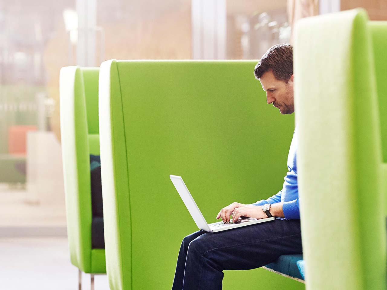 Man working on  laptop while sitting on a green chair