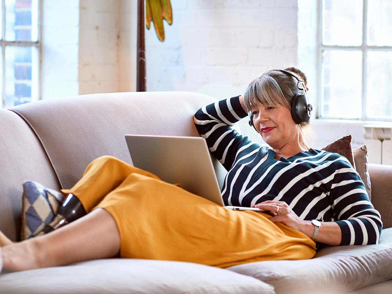 Woman on couch with headset reading a laptop.