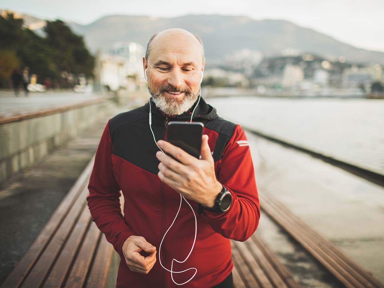 Older man out on a jog with headphones on looking at his mobile phone and smiling