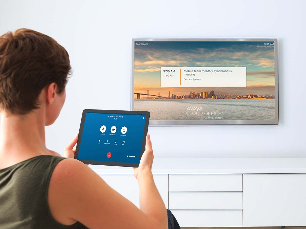 Woman using a tablet in her living room with a tv in background