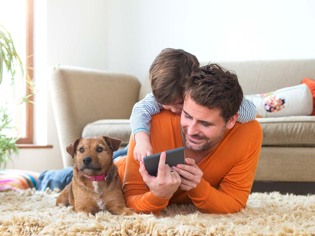 Man on floor looking at smartphone while child and dog are next to him.