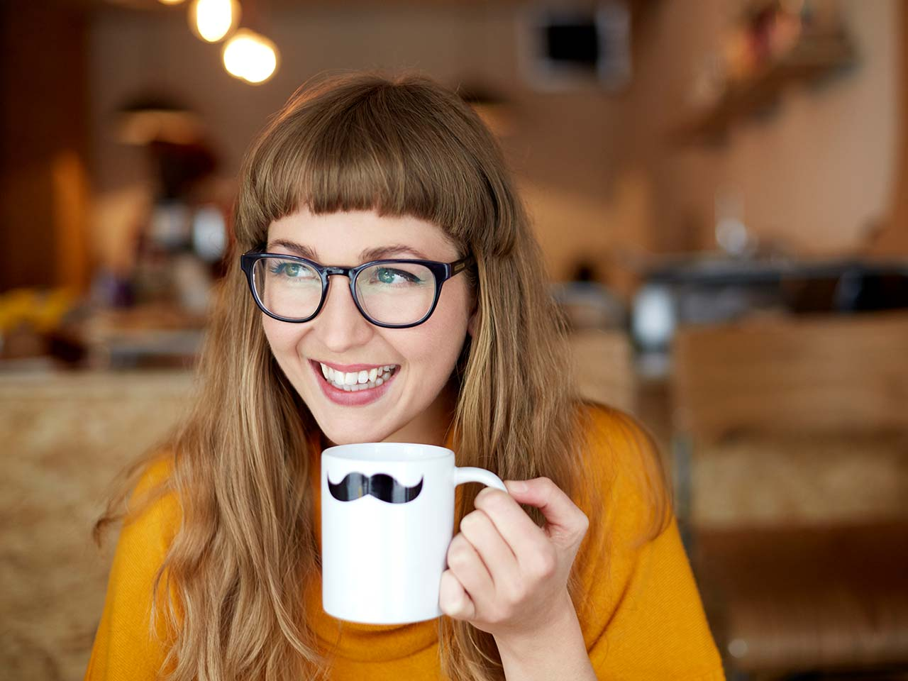 Red headed girl with glasses smiling and holding a coffee mug with a tiny mustache on it