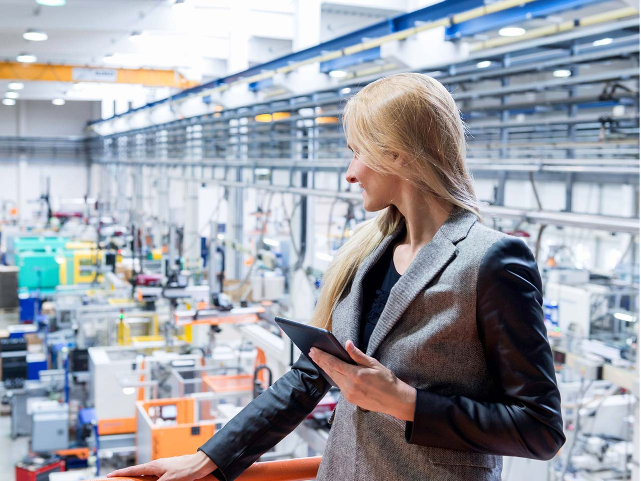 Woman working on a tablet looking out on factory floor