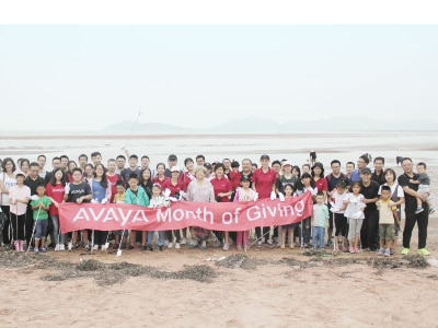 Avaya employees and their families posing on a beach with month of giving sign